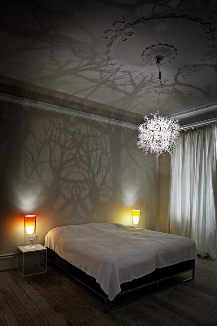 Light sculpture projecting tree shadows on the walls of a bedroom