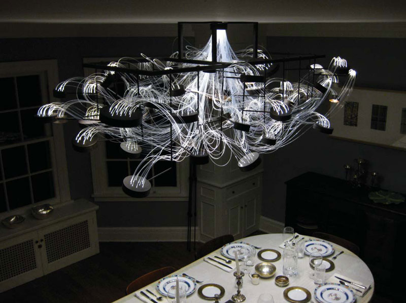 Bacterioptica Chandelier designed by Mad Lab attached to the ceiling in a dining room