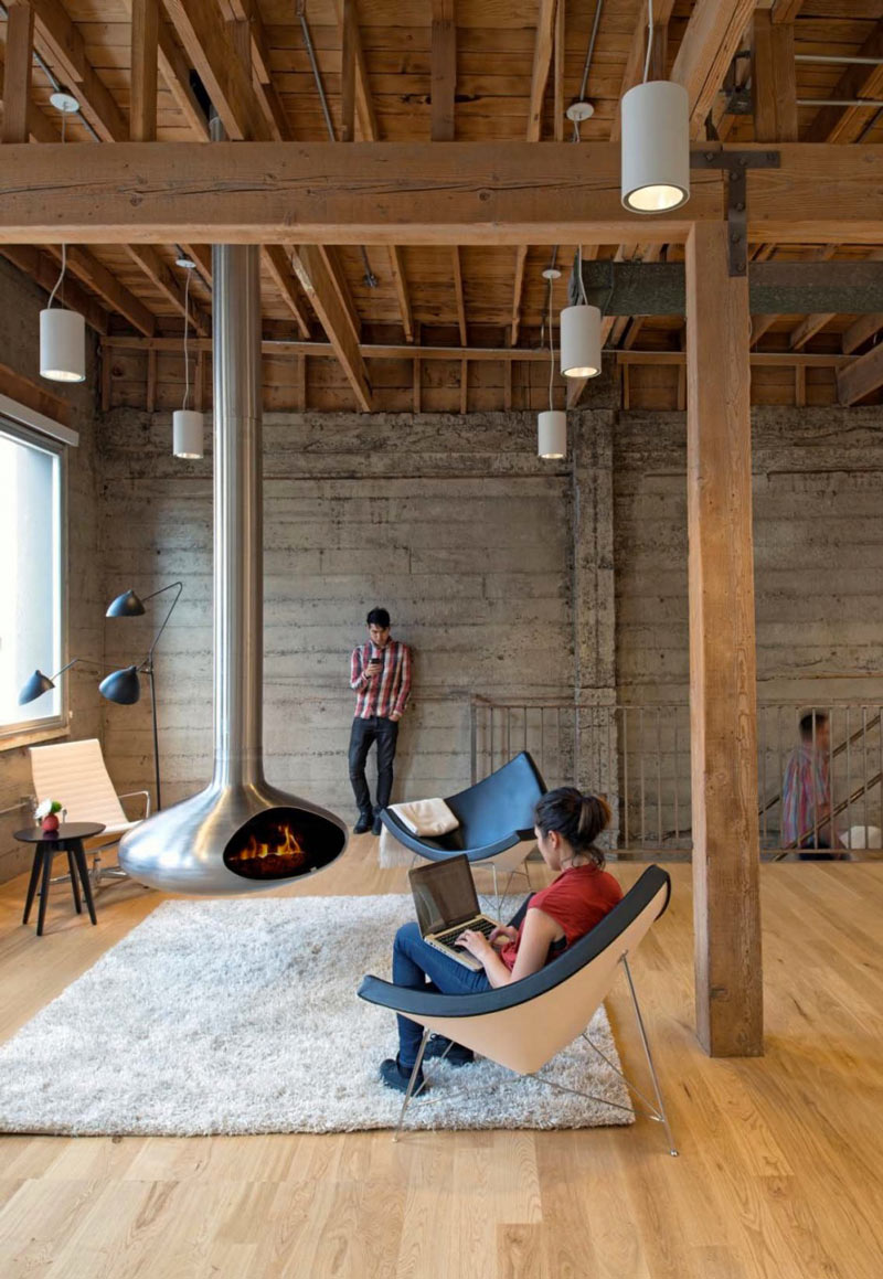 Employees around the fireplace and chimney in the center of a room at Giant Pixel Headquarters in San Francisco designed by Studio O+A