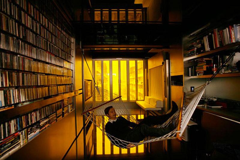 Gary Chang in a hammock of his Hong Kong micro apartment