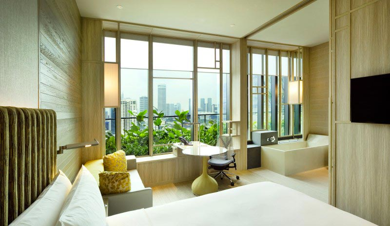 bed, chair and view from a hotel room at the Parkroyal Singapore