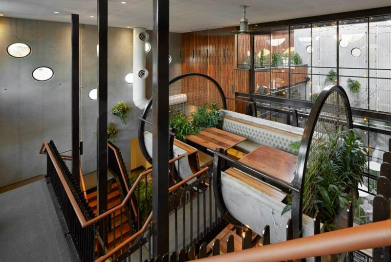 seating booth surrounded by green plants and stairs to the first floor at the Prahran Hotel
