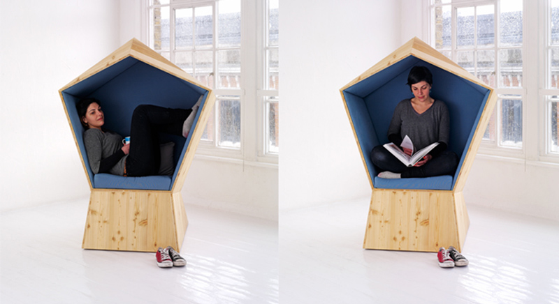 Front side view of the wooden made Quiet Chair by Studio TILT with a person inside reading a book