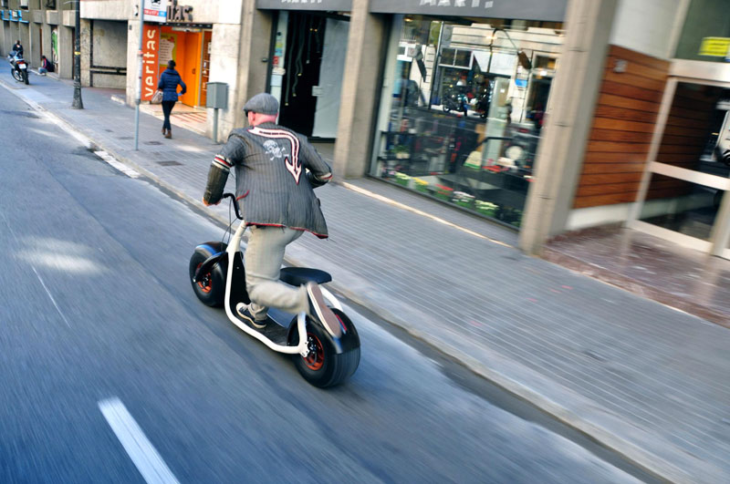Man cruising on the street on a white Scrooser