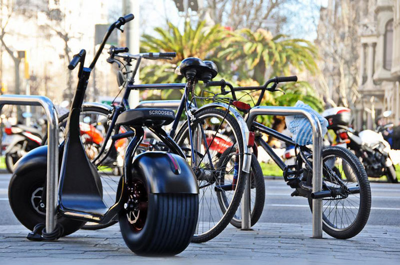 Black Scrooser motionless near other bicyles