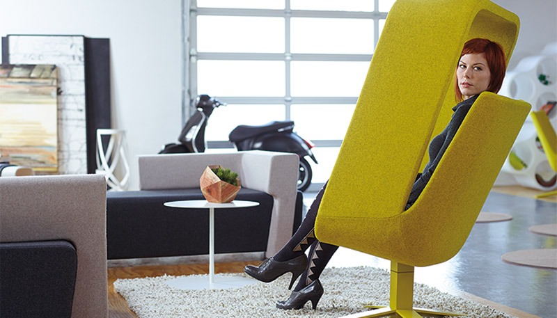 woman sitting in a yellow windowseat chair in a room - Haworth Chairs