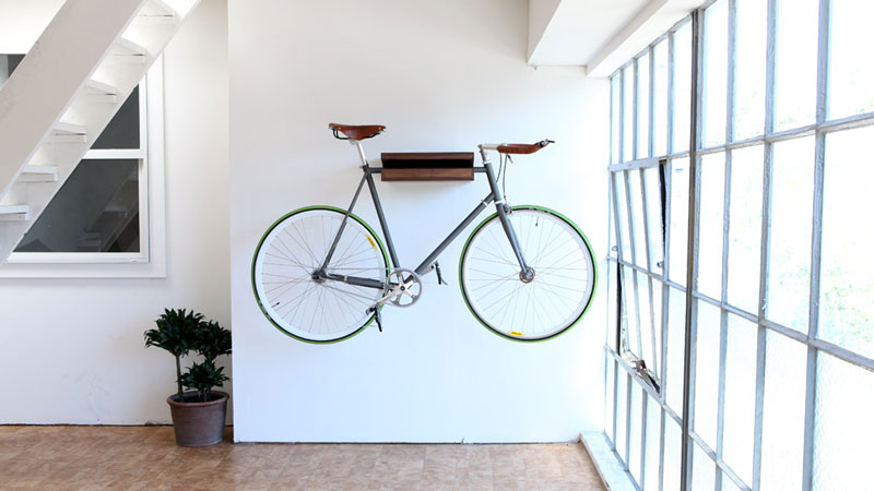 green bicycle suspended on a bookshelf in a white room