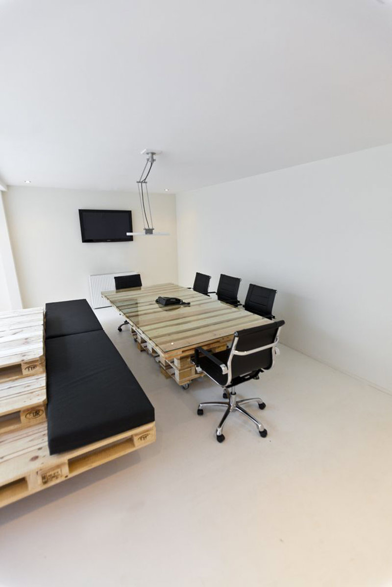 Pallet tables and black swivel chairs in a conference room at Brandbase Pallet Office by MOST Architecture