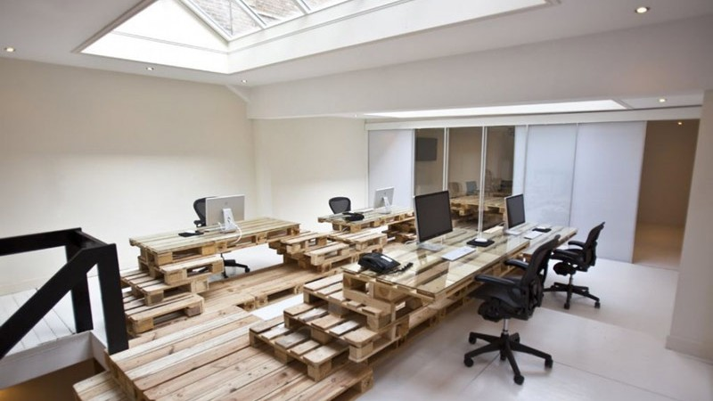 Pallet tables and swivel chairs with a skylight in a room with white walls at the Brandbase Pallet Office by MOST Architecture