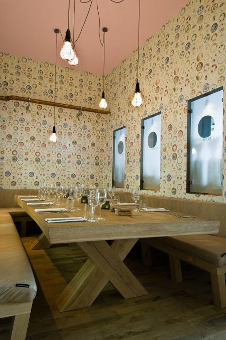 Long wooden table and benches at the Fabbrica Restaurant in Bergen by Tjep Studio
