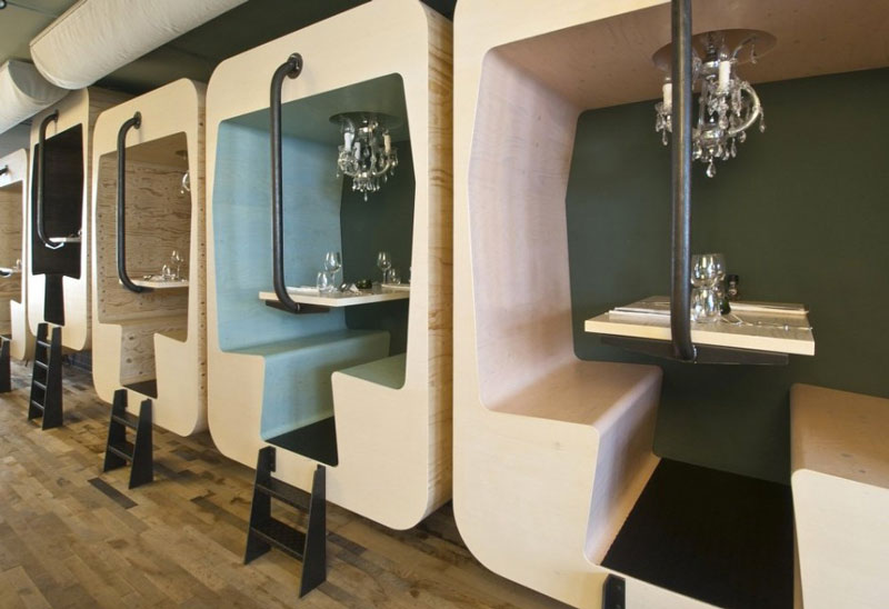Private booths accesible with short ladders at the Fabbrica Restaurant in Bergen by Tjep Studio
