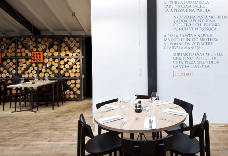 Round table and black chairs at the Fabbrica Restaurant in Bergen by Tjep Studio