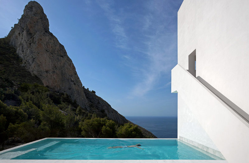 Woman swimming in a pool overlooking the scenery of an ocean at the House on the Cliff by Fran Silvestre Arquitectos