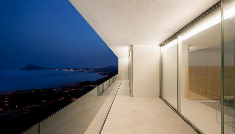 exterior patio and glass door of the House on the Cliff by Fran Silvestre Arquitectos