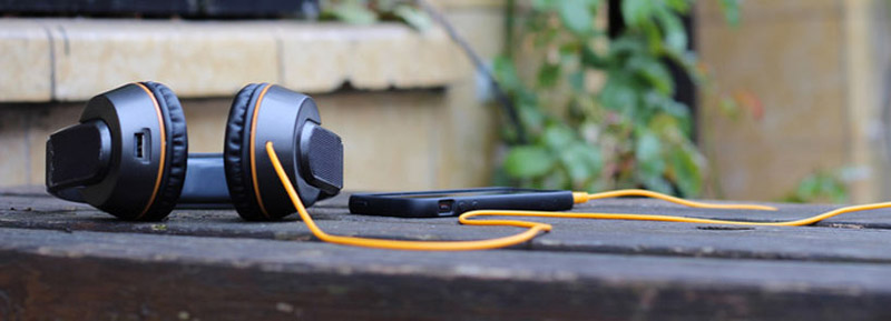 OnBeat solar powered headphones lying on a wooden table