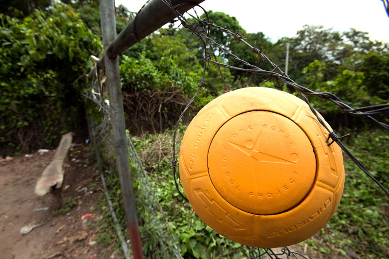 Yellow One World Futbol Soccer ball on a barb wire fence