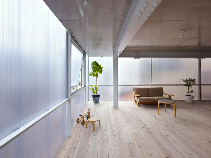 Walls and a tall plant at the House in Tosuien by Suppose Design Office