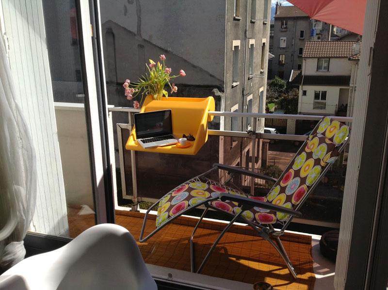 A computer on a yellow balKonzept Balcony Desk