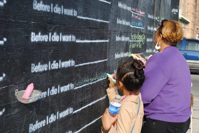 Little girl writing on the Before I Die wall by Candy Chang