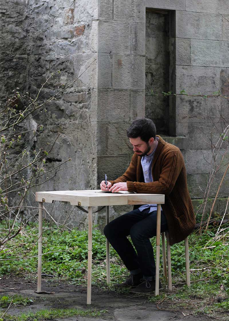 Man using the BOXED Multi Functional Furniture by Tyrone Stoddart as a desk outdoors