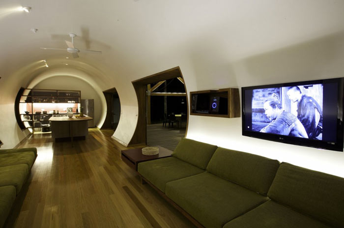 Living room with green couches at the Drew House by Simon Hills of Anthill Constructions