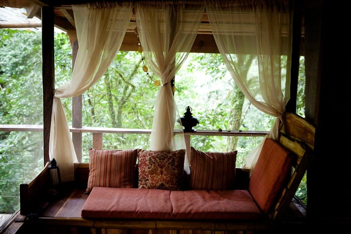 Couch with red pillows at the Finca Bellavista Treehouse Community in Costa Rica