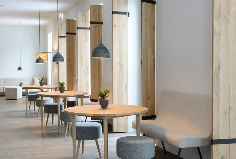 Dining area with tables and chairs at the Hotel Wiesergut in Hinterglemm Austria by Gogl Architekten