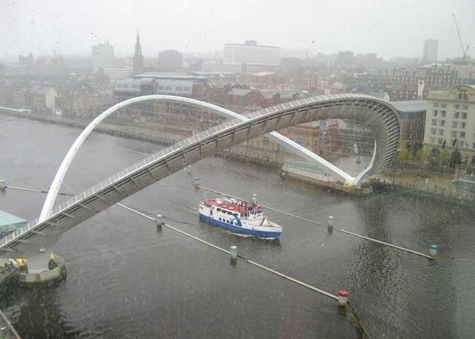 A boat passing under the Gateshead Millennium Bridge Tilting Bridge in England