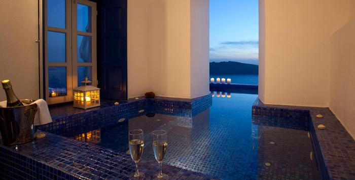 Champagne glasses ont the ledge of an indoor pool at the Ikies Traditional Houses in Santorini