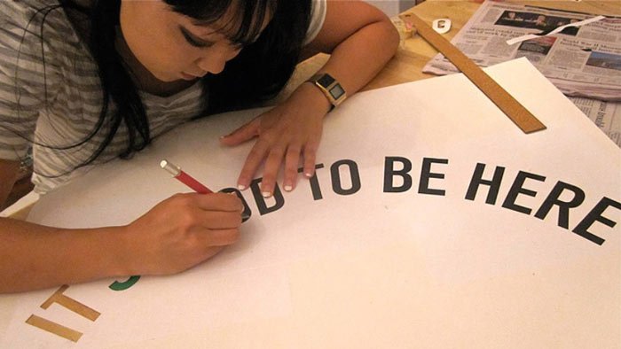 Candy Chang drawing the outline of 'It's Good to be Here'
