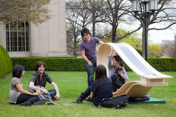 People using the MIT SOFT Rockers Solar Powered Charging Station & Rocking Chair