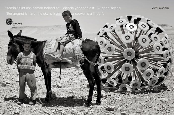 2 boys and a donkey in the desert pulling a Mine Kafon Minefield Sweeper