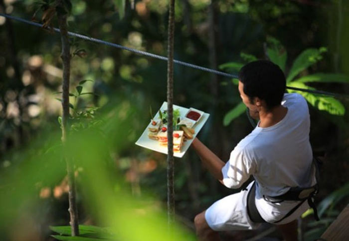 Man taking a plate of food to a Treepod at Soneva Kiri via zip line