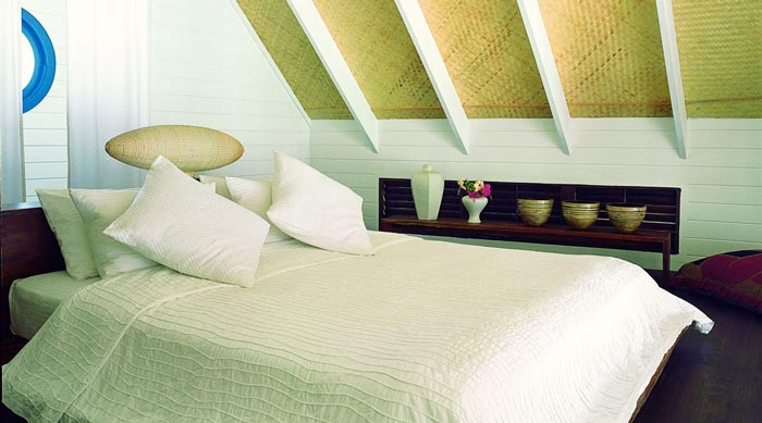Bed in a bungalow at Cocoa Island Resort in The Maldives by COMO Group