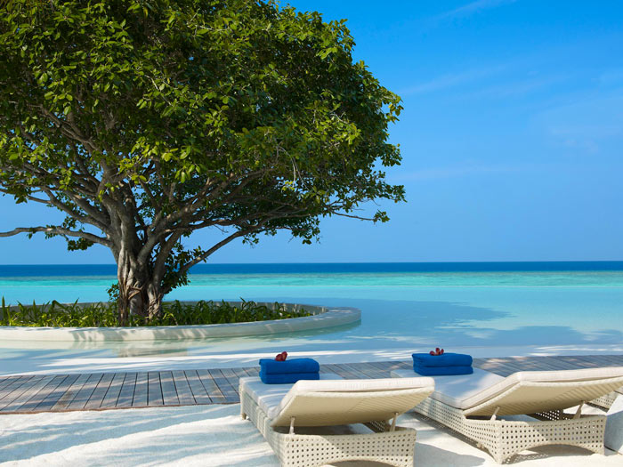 Lounge chairs and the sea at Dusit Thani Maldives Resort in Baa Atoll