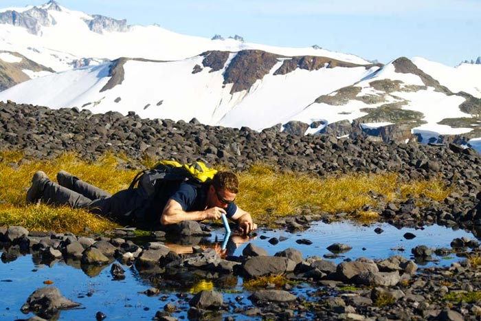 Man using the Lifestraw Portable Water Filtration System to drink water from a water stream