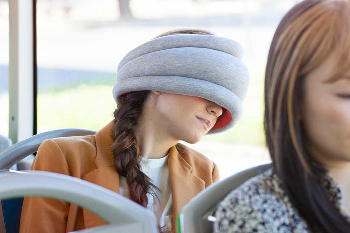 Women using the Ostrich Pillow Light in the bus