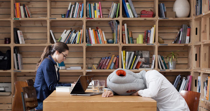 Man taking a nap using the Ostrich Pillow at the library