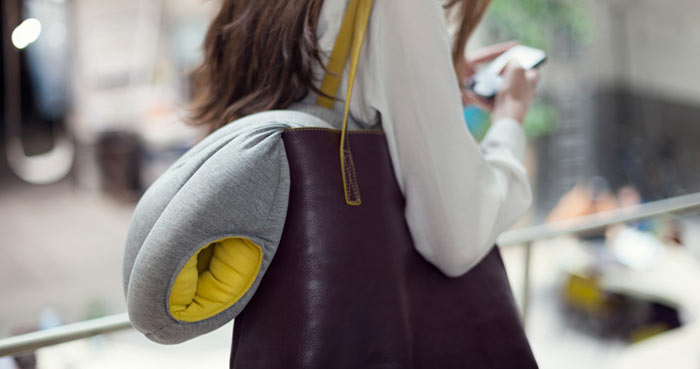 Woman carrying the Ostrich Pillow in her bag