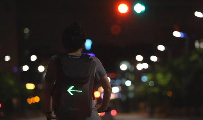 Cyclist using the SEIL Bag - An LED Backpack for Cyclists at night