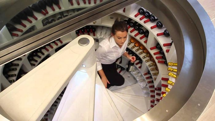 Woman going up the stairs of an Underground Spiral Wine Cellar by Spiral Cellars Ltd