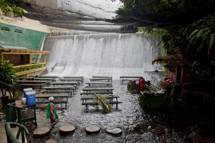 View of the waterfall and tables at the Villa Escudero Resort Waterfall Restaurant in the Philippines