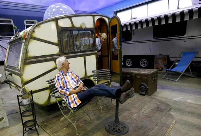 Man sitting on a chair on the front lawn of a trailer at Basecamp Bonn Young Hostel in Germany