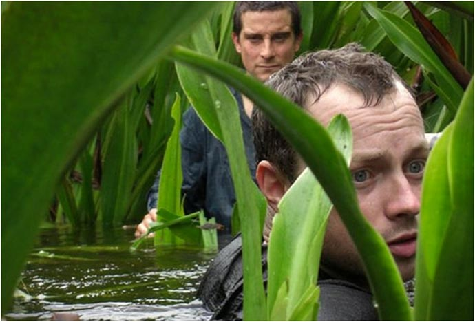 Men walking in shoulder high water during the Bear Grylls Survival Academy