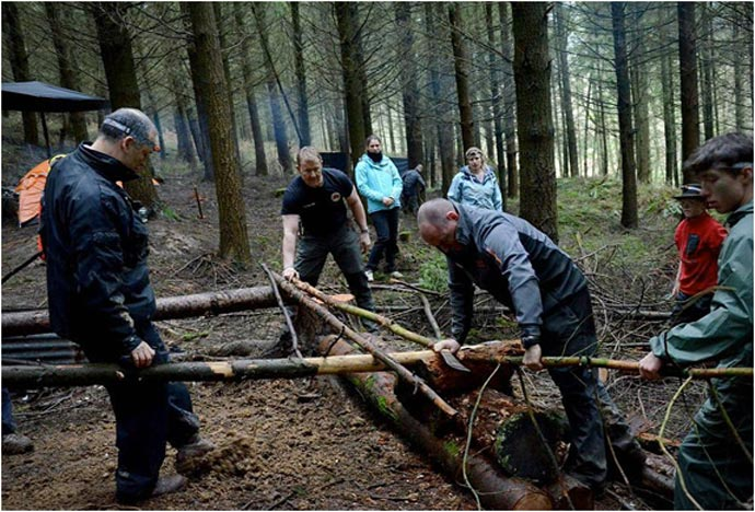 Men working with wood in the forest during the Bear Grylls Survival Academy