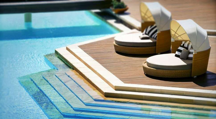 Swimming pool and lounge chairs at HAYMAN ISLAND RESORT in AUSTRALIA