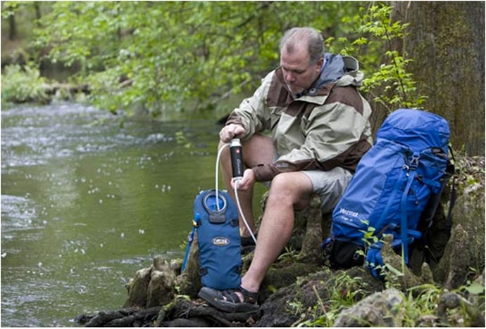 Man using the Katadyn Pocket Water Microfilter in a lake