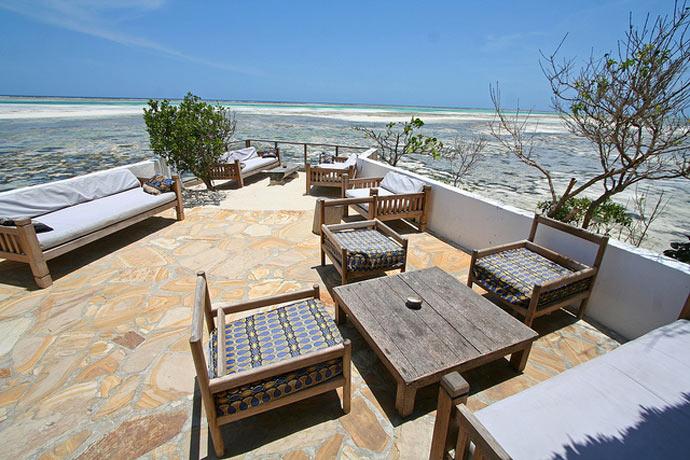 Terrace with wooden tables and chairs at The Rock Restaurant in Zanzibar