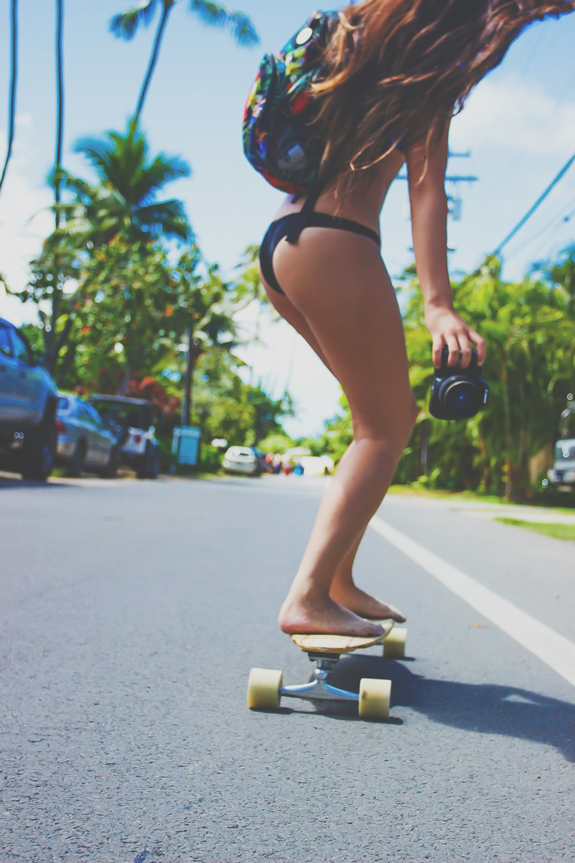Bikini barefoot girl riding a skateboard down the street with camera in her hands