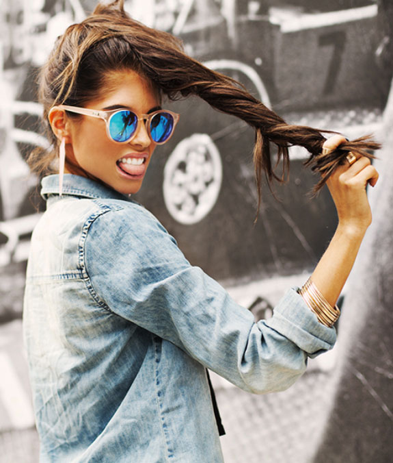 Urban dressed girl with a blue sunglasses pooling her pony tale